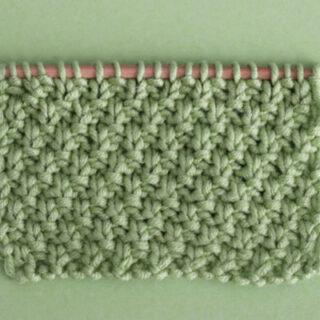 Irish Moss Stitch Knitting Pattern swatch on knitting needle atop a green background.