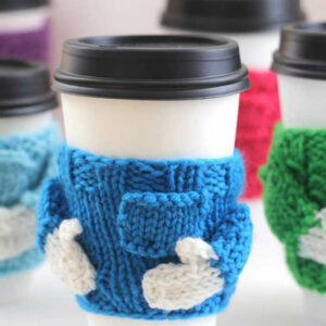 Knitted Mug Cozy with sweater shape in blue yarn on a coffee cup.