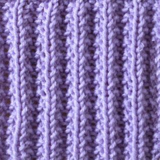 Seeded Rib Stitch pattern knitted in purple yarn.
