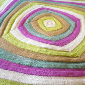 Colorful blanket knitted in the swirly square texture pattern.