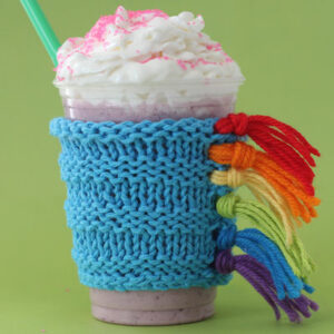 Knitted drink cozy in colorful unicorn design with fringe mane.