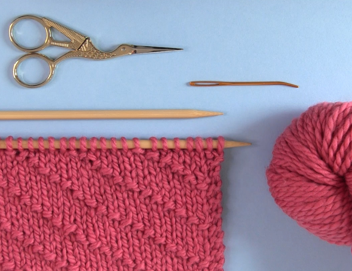 Knitted swatch of the diagonal seed stitch with yarn, knitting needles, scissors, and a tapestry needle.