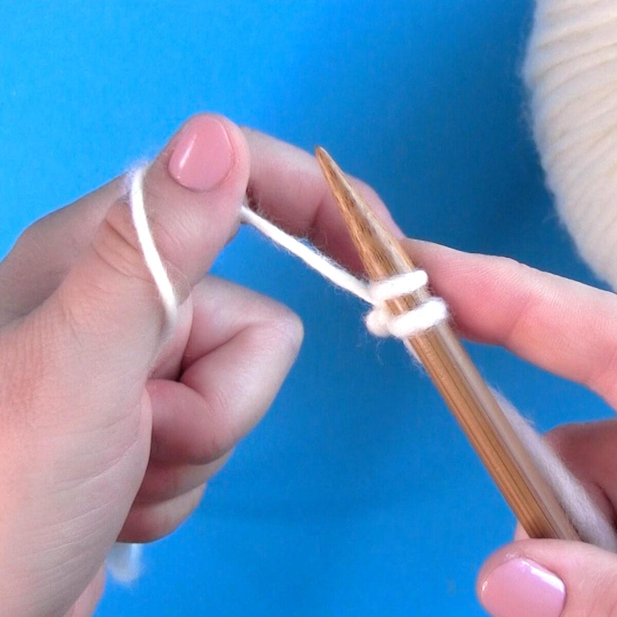 Método de fundición con el pulgar con hilo y una aguja de tejer sostenidos por las dos manos.