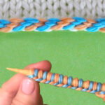 Hand demonstrating the 2-color braided cast on knitting technique.