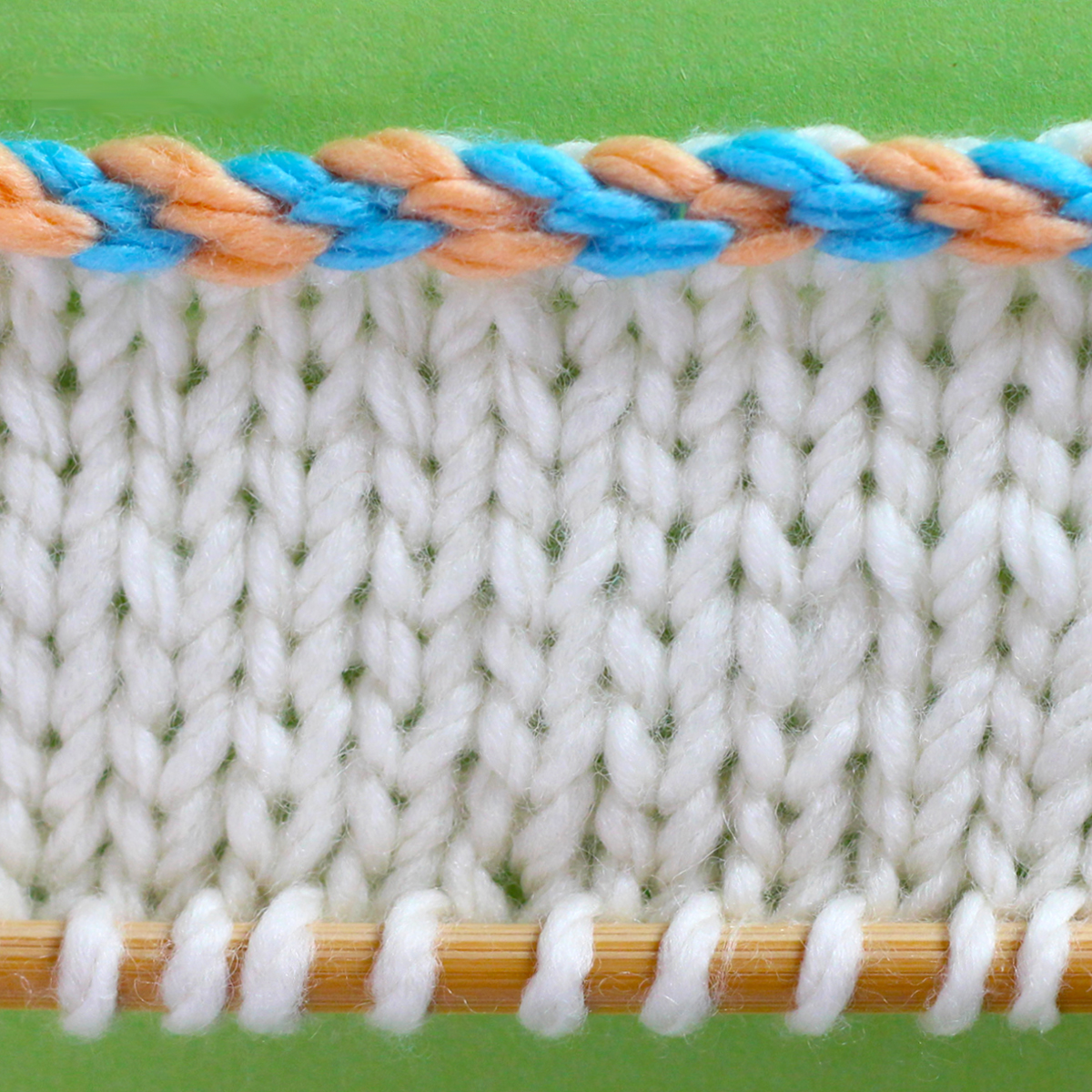 Knitted Swatch of stockinette with the edge in a 2-color braided cast on technique.