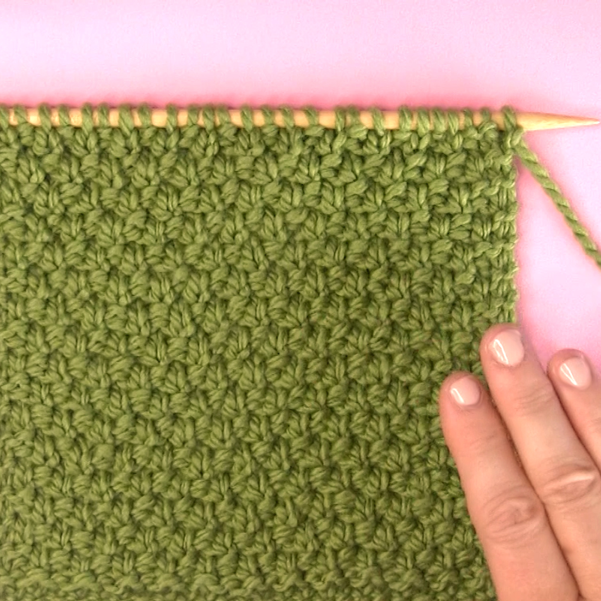 Irish Moss Knit Stitch pattern on knitting needle in green color yarn with woman's hand.