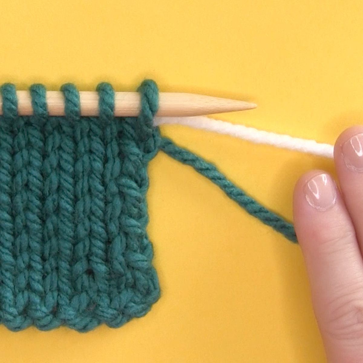 Knitted swatch with new yarn color introduced at the beginning of a row.