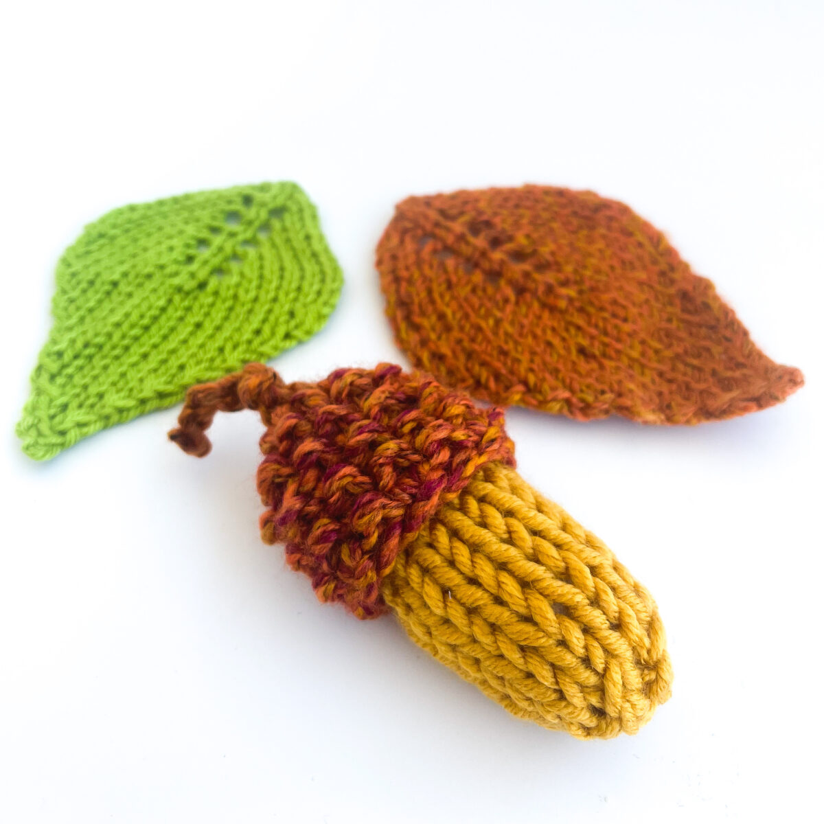 Knitted acorn with two knitted leaves.